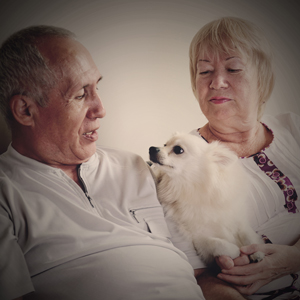 An older couple holding a dog