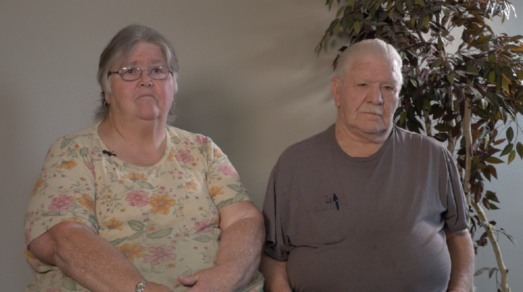 Image of an older man and woman sitting next to a potted plant.