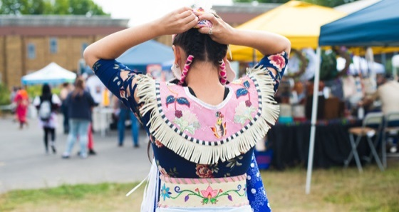 Image of a young Native girl wearing traditional tribal dress, seen from behind.