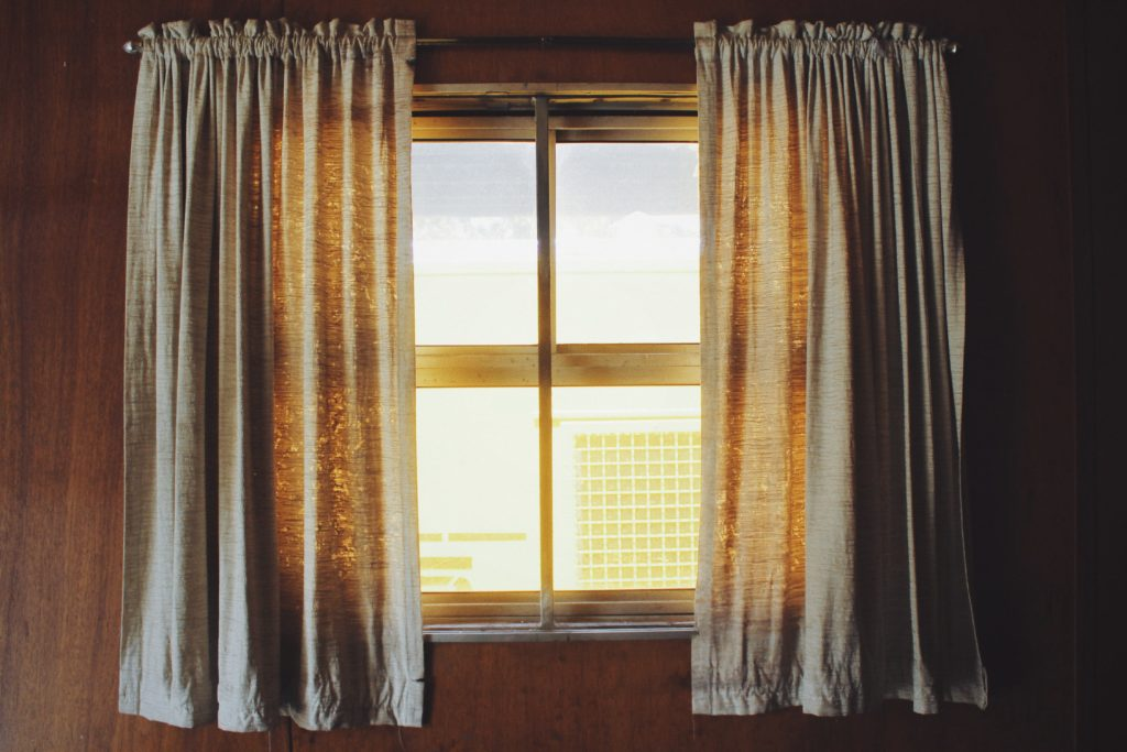 Image of a sunny window with draping curtains.