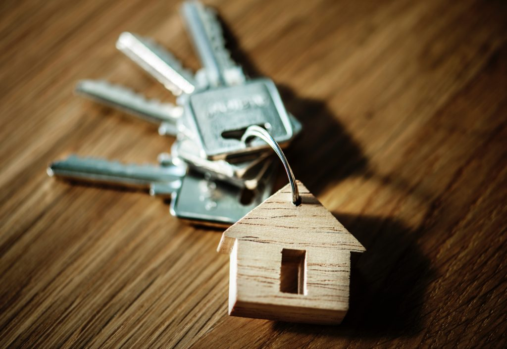 Image of a key chain with four keys and a small wooden house.