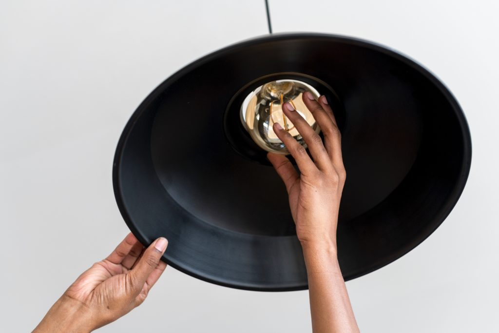 Image of a hand screwing in a bulb to a ceiling lamp.