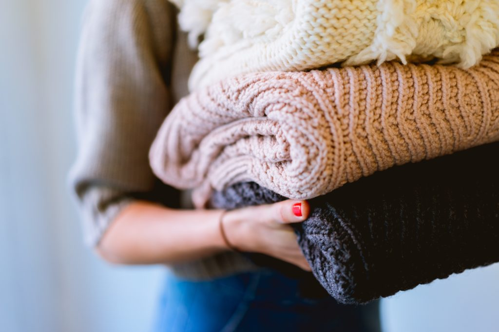 Image of a person holding a stack of folded blankets and sweaters.