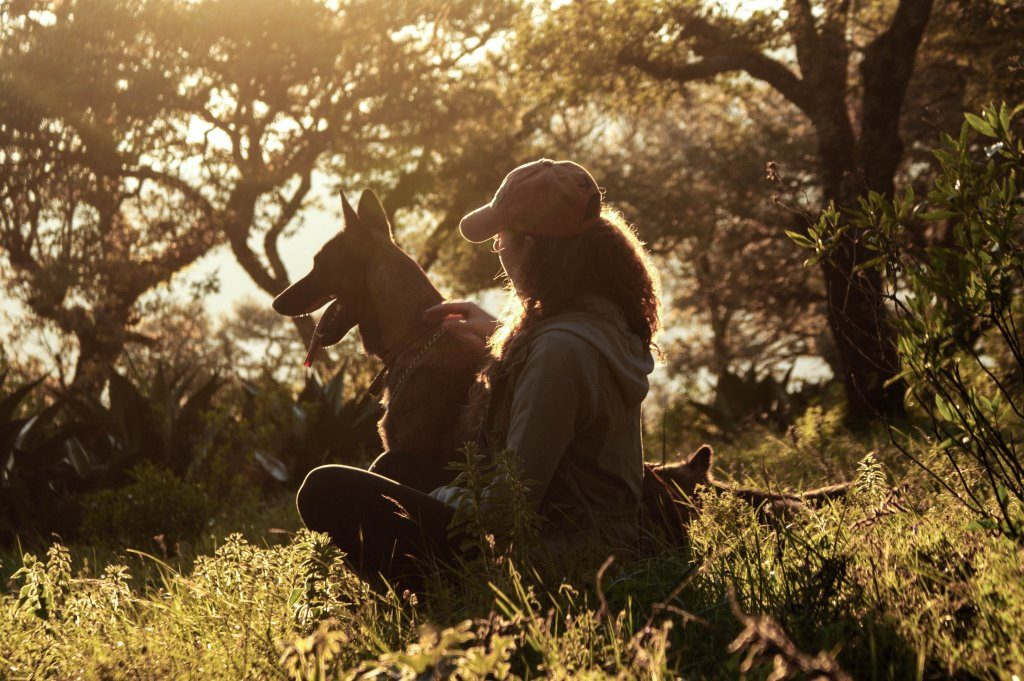 Image of a woman in a baseball cap and her dog sitting in front of trees.