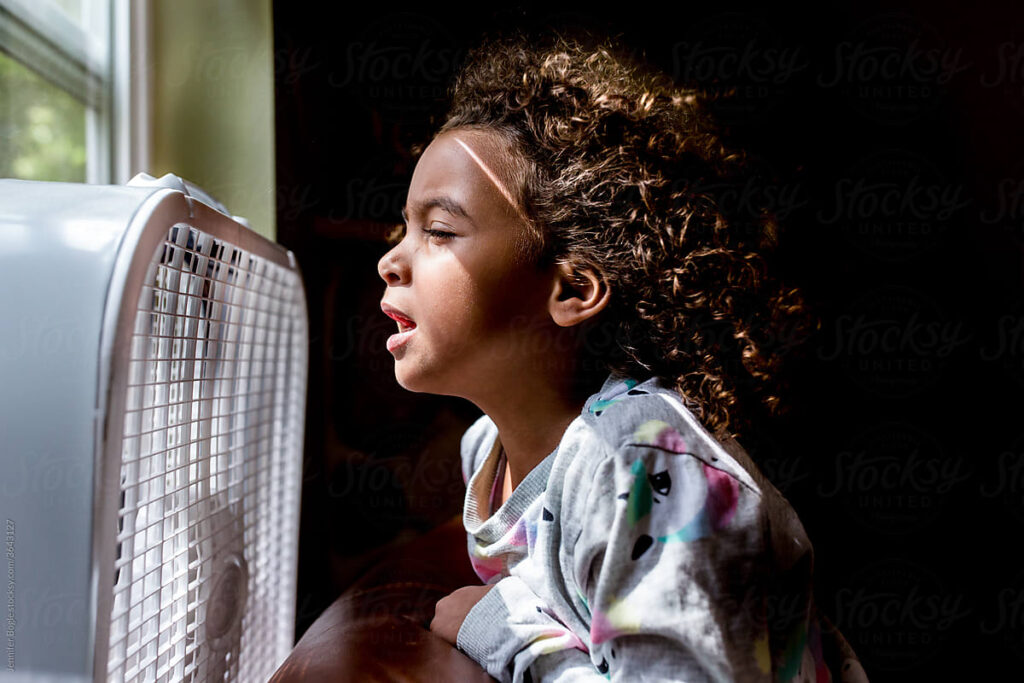 A young girl cools her face in front of a fan